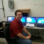 Engineering Innovation employee, Aaron Pedigo, smiling while sitting in an office with four laptops lined up on a desk behind him.