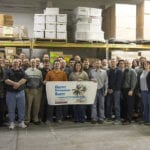 """Group of Engineering Innovation employees standing in a warehouse holding a sign that says """"Happy Retirement Sue!"""""""