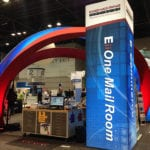 """Engineering Innovation's booth with large red arches and a column saying """"E.i.i. One Mail Room"""" at the 2016 IRCE trade show."""