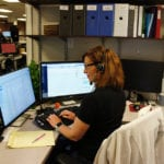 A female customer support representative wearing a headset is sitting at her desk and typing on her keyboard.