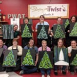 Group of female Engineering Innovation employees in a painting studio each holding a painting of a Christmas tree.