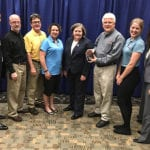 A group of Engineering Innovation employees poses for a photo with the Postmaster General while accepting the 2017 USPS award.