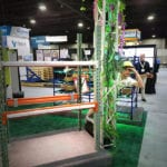 Engineering Innovation employee, Nick Ambrose, wearing a safari hat and peaking out from behind a truss at the Engineering Innovation jungle-themed trade show booth.