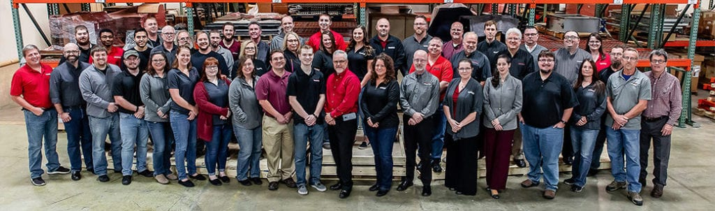 Engineering Innovation staff group photo in a warehouse.