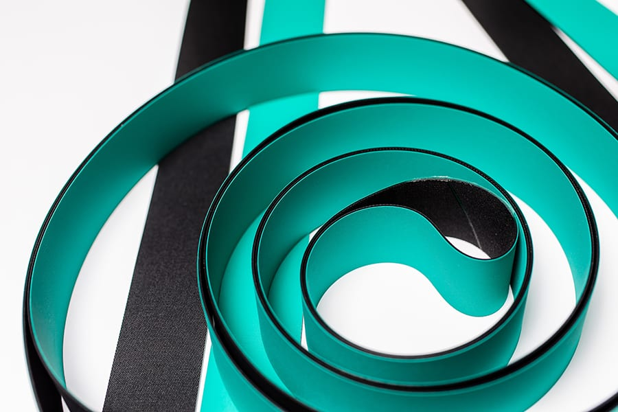A turquoise and black machine belt on a white background.
