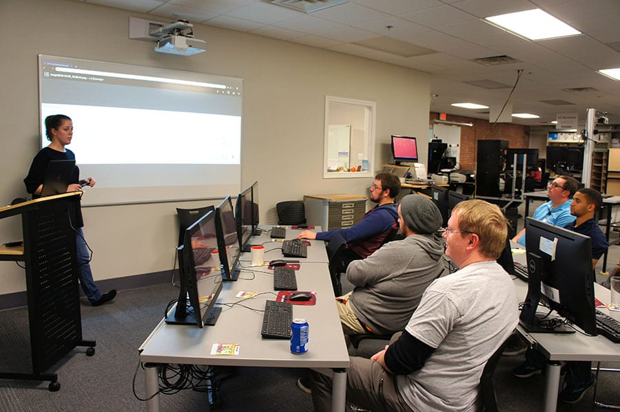 Customer support technician, Rebecca Irrgang, stands in front of a projector screen while leading a training session for Engineering Innovation employees.