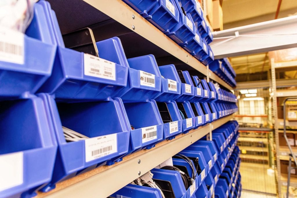 A rack filled with blue tubs of machine replacement parts and supplies.