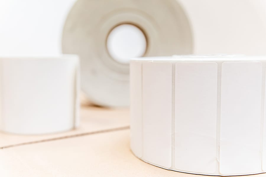 Three rolls of white labels sitting on top of a tan surface.