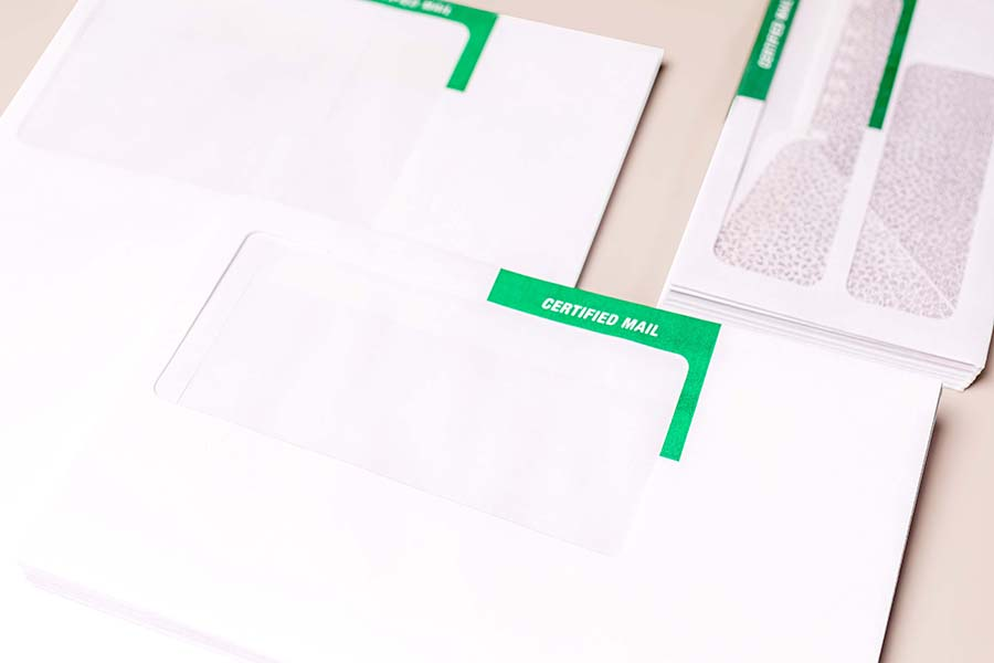 Three stacks of certified mail envelopes on a tan background.