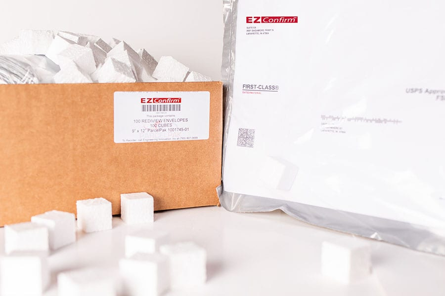 "A cardboard box filled with small, white, Styrofoam cubes and a large, white first-class envelope both labeled with an ""EZ-Confirm"" logo."