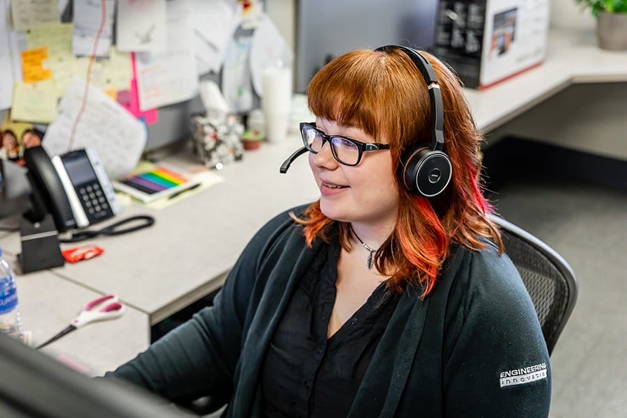 Happy female customer support technician wearing a headset and looking at her computer screen.