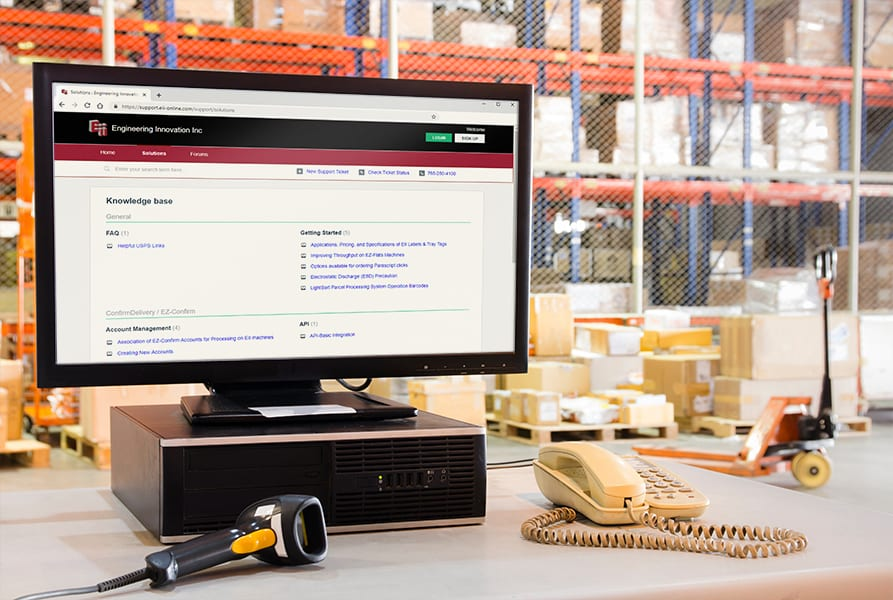 Close up of a computer in a warehouse with the Engineering Innovation knowledge base website open in a browser.